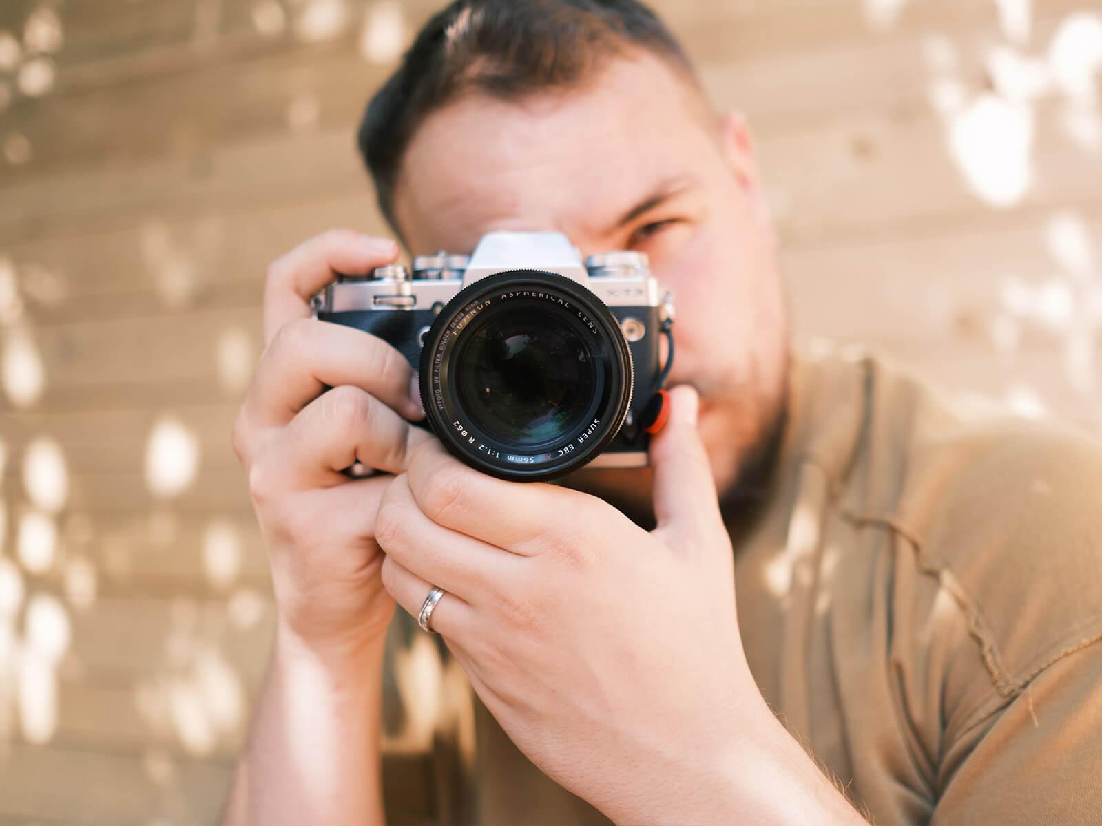 osoba drziaca fotoaparat